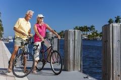 Couples supérieurs heureux sur des bicyclettes par une rivière Photo stock