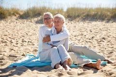 Couples supérieurs heureux étreignant sur la plage d'été Images stock