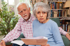 Couples supérieurs passant par des finances semblant inquiétées Photographie stock libre de droits