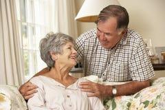 Couples supérieurs retirés se reposant sur Sofa At Home Together Photographie stock libre de droits