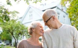 Couples supérieurs étreignant au-dessus du fond vivant de maison Photographie stock
