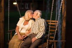 Couples sur des baisers d'oscillation de porche Photographie stock