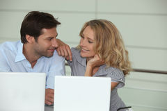 Couples sur des ordinateurs portatifs Photo stock