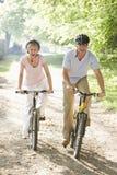Couples sur des vélos souriant à l'extérieur Photographie stock libre de droits