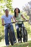 Couples sur des vélos souriant à l'extérieur Images stock