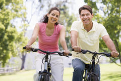 Couples sur des vélos souriant à l'extérieur Image libre de droits