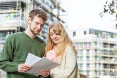 Couples sur l'avant du chantier de construction Maisons d'immeubles?, appartements à vendre ou pour le loyer Photos libres de droits