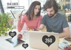 Couples sur l'ordinateur portable avec des barres de statut de goûts Photographie stock libre de droits