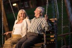 Couples sur l'oscillation de porche, égalisant Photo stock