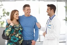 Couples sur la consultation de grossesse avec le docteur photographie stock libre de droits