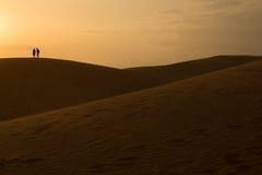 Couples sur la dune de sable dans le désert, ciel de coucher du soleil Photos stock