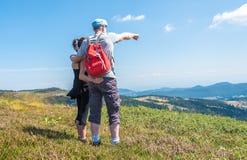 Couples sur la hausse regardant le paysage Photos stock