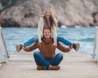 Couples sur la jetée en bois près de la mer en automne Image stock