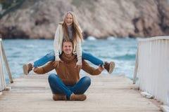 Couples sur la jetée en bois près de la mer en automne Images stock