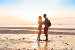 Couples sur la plage aux vacances d'été de coucher du soleil, les beaux jeunes dans l'amour, femme d'homme tenant des mains Image libre de droits