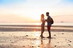 Couples sur la plage aux vacances d'été de coucher du soleil, les beaux jeunes dans l'amour, femme d'homme tenant des mains Images stock