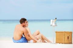 Couples sur la plage avec Champagne Picnic de luxe Image libre de droits