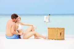 Couples sur la plage avec Champagne Picnic de luxe Photos libres de droits