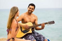 Couples sur la plage avec la guitare Images libres de droits