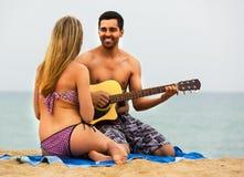 Couples sur la plage avec la guitare Photographie stock