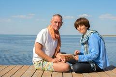 Couples sur la plage avec le PC de comprimé Photo libre de droits