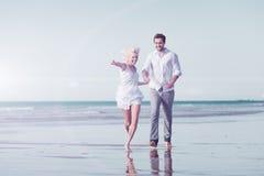 Couples sur la plage dans des vacances de lune de miel photos stock