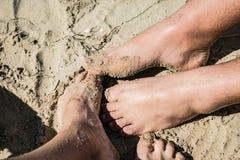Couples sur la plage Fermez-vous vers le haut de l'image de jambes photos libres de droits