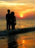 Couples sur la plage. lever de soleil. Images libres de droits