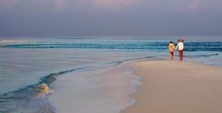 Couples sur la plage sablonneuse marchant et tenant des mains Photographie stock