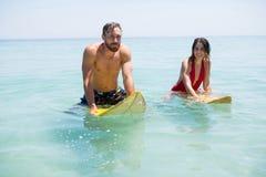 Couples sur la planche de surf en mer Images stock