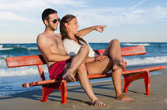 Couples sur le banc au bord de la mer Photos stock