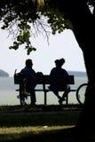 Couples sur le banc de stationnement Photographie stock
