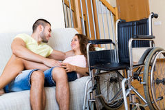 Couples sur le divan près du fauteuil roulant Photo stock