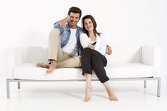 Couples sur le divan regardant la TV Photographie stock