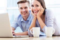 Couples sur le plancher utilisant l'ordinateur portable Images stock