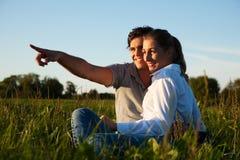 Couples sur le pré dans le coucher du soleil Photo libre de droits