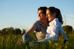 Couples sur le pré dans le coucher du soleil Photographie stock libre de droits