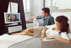 Couples sur le sofa avec l'extérieur de TV Photos stock