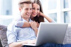 Couples sur le sofa avec l'ordinateur portable photo libre de droits