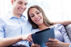 Couples sur le sofa avec le comprimé numérique Images libres de droits