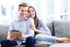 Couples sur le sofa avec le comprimé numérique Photos libres de droits