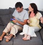 Couples sur le sofa jouant des jeux vidéo Photographie stock libre de droits