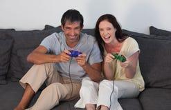 Couples sur le sofa jouant des jeux vidéo Photo stock