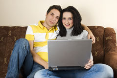 Couples sur le sofa utilisant l'ordinateur portatif Photos stock