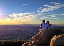 Couples sur le sommet de montagne observant un coucher du soleil avec vue sur le paysage urbain Photos stock