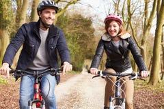 Couples sur le tour de cycle dans la campagne d'hiver Image stock