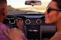 Couples sur le voyage par la route conduisant dans la voiture convertible Images stock