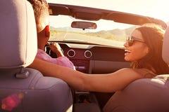 Couples sur le voyage par la route conduisant dans la voiture convertible Photos stock