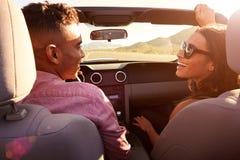 Couples sur le voyage par la route conduisant dans la voiture convertible Image stock