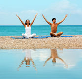 Couples sur le yoga de pratique de plage Photo stock